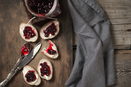 Sandwiches with butter and cranberry jam, messy spoon and knife on wooden cutting board with gray linen napkin. Top view point.