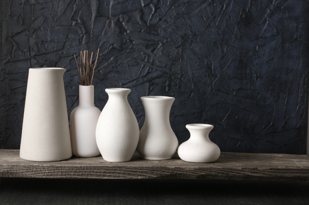 White Ceramic Vases On Distressed Wooden Shelf Against Rough Stock