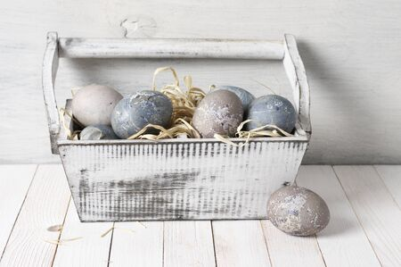 Natural dyed grey Easter eggs in shabby white box with straw on white rustic wooden background. Banque d'images