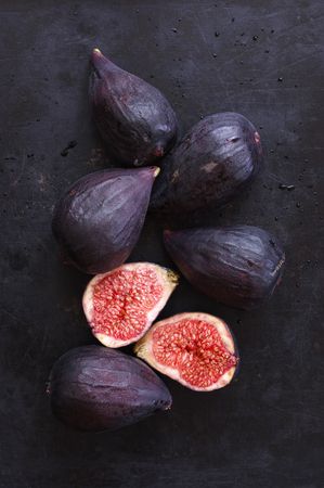 Ripe purple whole and cut figs on black background. Top view point. Dark moody image. 写真素材