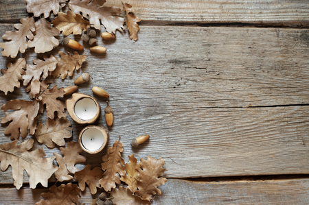 Autumn dry oak leaves with acorns and candles on old rustic wood background. Top view point.