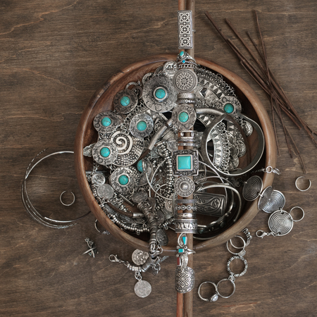 Boho style rings set on wooden sticks and bowl with assorted bohemian chic silver jewelry on wood background. Top view point. Stock Photo