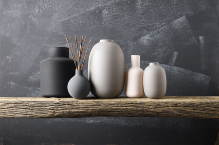 Home decor - various neutral colored vases with wood sticks on rough distressed wooden shelf against grey wall.