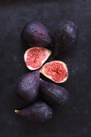 Wet ripe purple whole and cut figs on black background. Top view point. Dark moody image. Archivio Fotografico