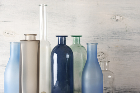 Set of various muted colored glass bottles against white shabby wooden wall .