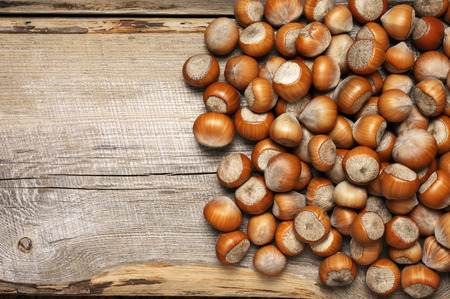 Unpeeled hazelnuts heap on vintage wooden background. Top view point.