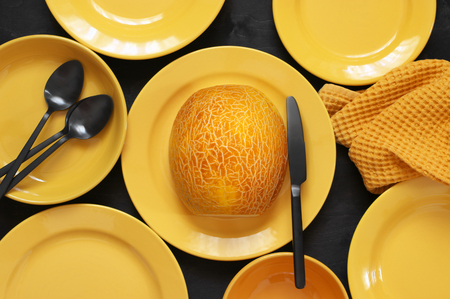 Half of melon in plate and  yellow tableware on black wood table. Top view point. Stock Photo