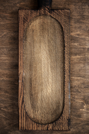 Old grungy oak wood cutting board on wooden table.