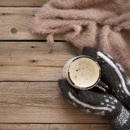 Woman hands in warm wool mittens embracing of hot coffee mug on rustic wooden table. Top view point. Stock Photo