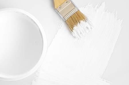 White paint in bucket, brush and stroke on white background. Top view point.