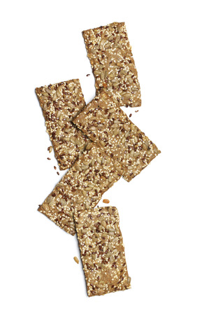 Crispy rye flatbread crackers with sesame and sunflower seeds isolated on white background. Top view point. Stock Photo