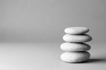 Stack of grey massage stones on gray background.