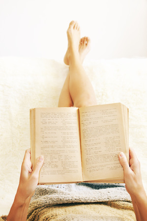 Woman is lying feet up on white shaggy blanket and reading book. Cozy leisure scene. Text in book is unreadable.