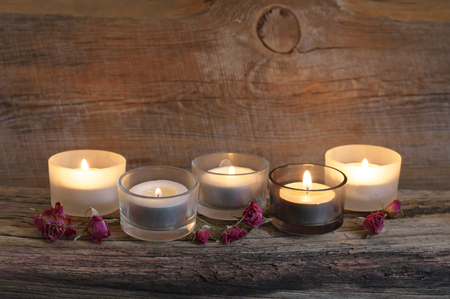 Burning candles and dried roses on old weathered wood against rustic wooden wall at background.