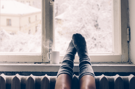Cozy winter still life: woman legs in warm woolen socks and mug of hot beverage on old windowsill against snow landscape from outside.