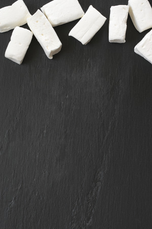 White homemade marshmallow as border on black slate. Top view point. 스톡 콘텐츠