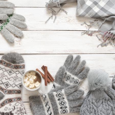 Tricots en laine gris chaud : chaussettes, gants, bonnet, écharpe et tasse de cacao avec guimauve sur fond de bois rustique blanc. Hiver confortable nature morte.