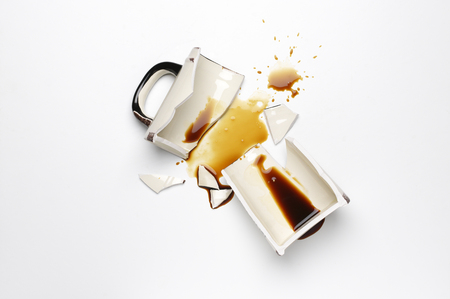 Broken ceramic mug with spilled coffee on white background. Top view point.