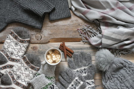 Warm grey woolen knitwear: socks, pom hat, scarf and cup of cocoa with marshmallow on rustic wood background. Winter cozy still life.