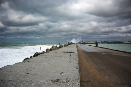 Concrete breakwater in stormy sea under dark cloudy sky.