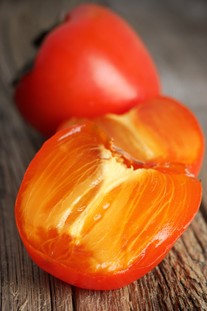 Cut ripe persimmon close-up on rustic wood. Stockfoto - 116162994