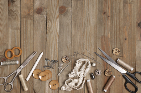 Set of sewing tools and accessories on rustic wooden background. Top view point.