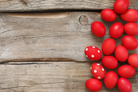 Pile of traditional red Easter eggs on old distressed wood background. Top view point.