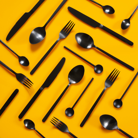 Set of black steel cutlery on bright yellow background. Top view point. Stock Photo