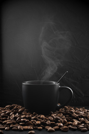 Black cup of hot coffee with steam in coffee beans on dark background.