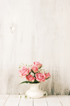 Fresh flowers bouquet of pink roses in ceramic vase on white wood table against rustic shabby wall. Banco de Imagens