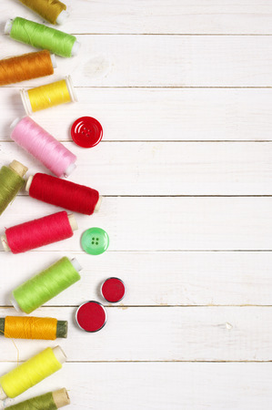 Set of sewing colorful spools and buttons on white wooden background. Top view point. 版權商用圖片