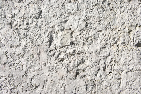 Old rough whitewashed limestone wall texture as background.