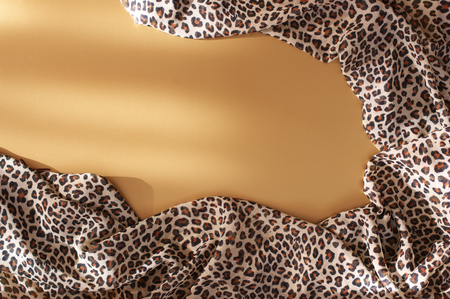Animal print textile scarf on matt gold background in sunlight. Top view point. Zdjęcie Seryjne