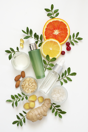 Composition of natural organic cosmetics, ingredients and leaves on white background. Top view point, flat lay.