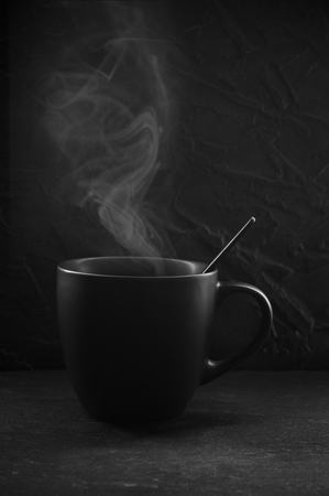 Black cup of hot coffee with steam on dark background.