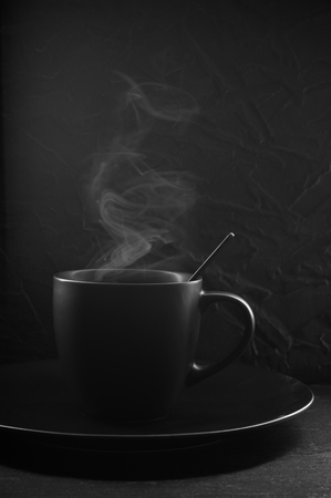 Black cup of hot coffee with steam in plate on dark background.