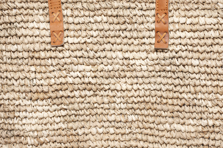 Woven natural straw texture with leather handles as background.