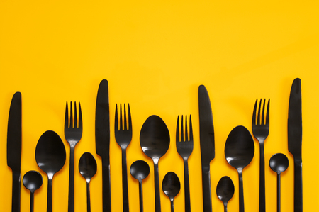 Set of black steel cutlery on bright yellow background. Top view point. 版權商用圖片