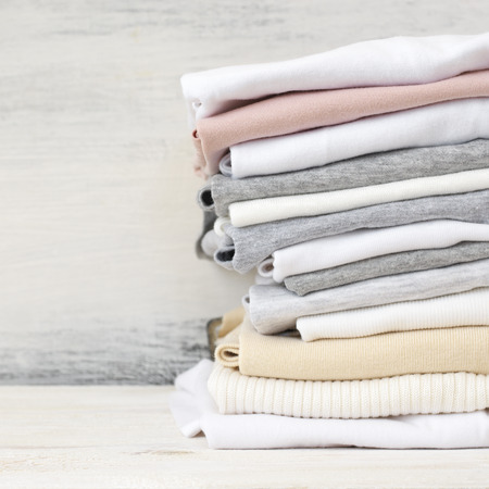 Stacked neutral colored t-shirts and tops on white wood background.