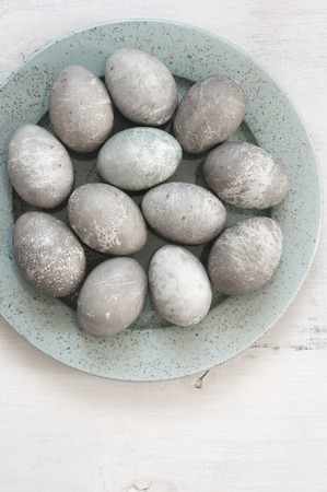 Creative unusual grey Easter eggs in ceramic plate on white wooden background. Top view.