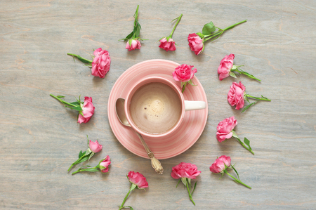 Pink cup of creamy coffee among flowers decor on warm grey wooden table. Top view, flat lay.
