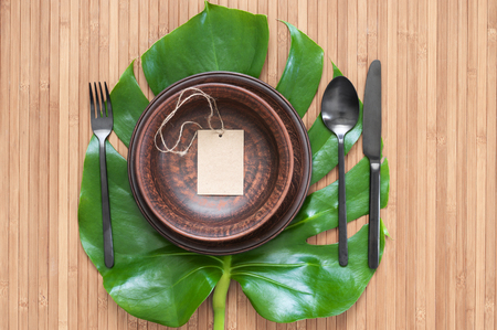 Exotic tropical eco style table setting with ceramic plates, black silverware and label on monstera leaf. Top view point.