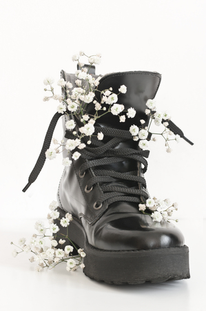 Black combat boot decorated of gypsophila flowers on white background.