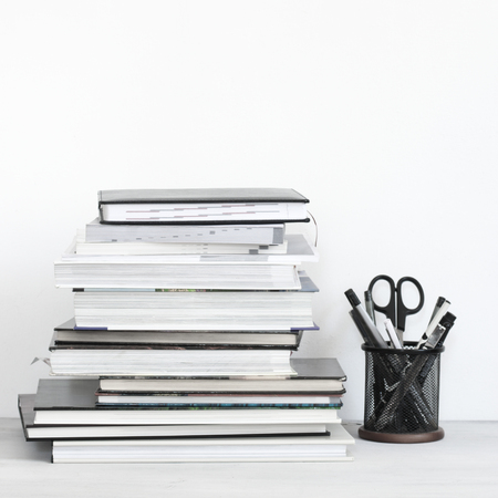 Stack of neutral colored books and stationery set on desk against white background. Standard-Bild