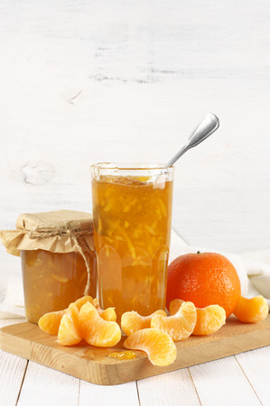 Citrus jam in glass jars and orange slices on cutting board against white rustic wooden wall.