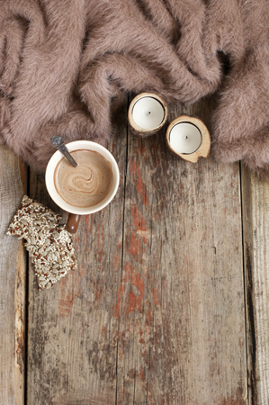 Warm soft blanket, cup of hot chocolate, candles and crackers on old rustic wood background. Cozy still life. Top view point.