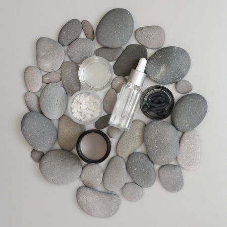 Natural organic cosmetics in grey pebble on gray background. Top view point, flat lay. Фото со стока