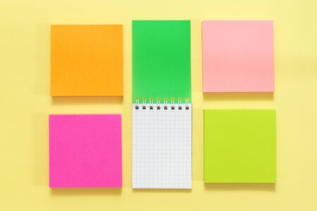 Colorful stationery set on yellow paper background. Top view, flat lay.