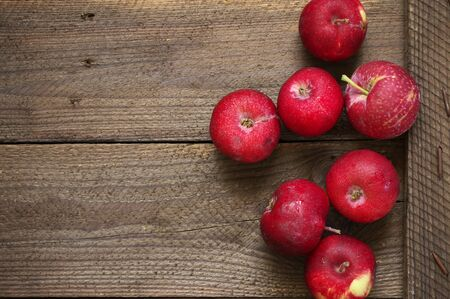 Organic red apples on brown rustic weathered wood. Top view.