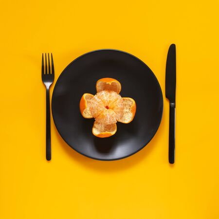 Peeled tangerine in black plate on bright yellow background. Top view point.